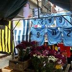 Barraquinha com bandeiras e camisas
