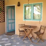 Our room's entrance and private terrace.. With wooden chairs, table and a windchime..