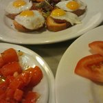 Three tapas: Carrots in dressing, quail eggs and chorizo on baguette; marinated tomatoes