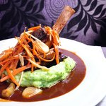 lamb shank braised in red wine with garlic confit, roasted vegetables and mashed potatoes with h