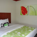 One of the beds w/ flower painting on wall