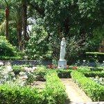 Rosedales rodeados de estatuas y otras flores.