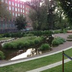 Small park next to hotel along the river, stream is fed by system to divert the river along the
