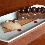 Chocolate brownie with milk chocolate mousse and cherries.