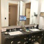 Sinks and mirror w TV of Deluxe 1-Bedroom Suite