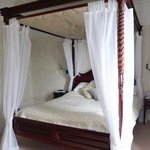 Room with four poster bed.