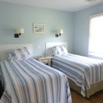 one of the bedrooms has two twin beds, a TV, dresser and closet space