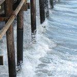 The waves crash against the pier