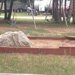 Sandbox with boulder in it.