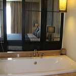 sliding shutters between the bathtub and bed