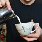A member of Homemade by Mann's staff expertly pouring milk to make a latte