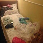 Pequeña cama (mientras preparaba maletas) Se ve llena con tres cosas encima.