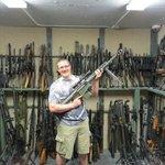 Chris hold a Barrett .50 cal sniper rifle in the gun vault