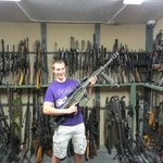 Alex holding a Barrett .50 cal sniper rifle in the gun vault