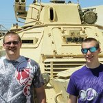 Chris and Alex in front of an armored vehicle