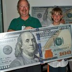 Posing with a large $100 bill