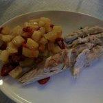 Una porzione di un bel branzino da chilo, al forno con patate e pomodorini.