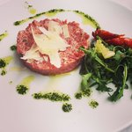 Steak Tartare with Parmesan shaving drizzled with herb oil.