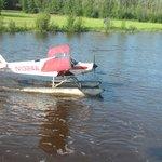 Float plane landing next to riverboat