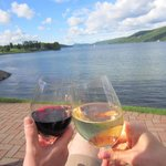 Enjoying a glass of wine on a bench by the lake. What a view!