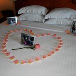 rose petals & family photos on bed