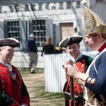 Reenactors chat in front of the Wheelwright Shop