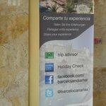 Cartel en recepción animando a compartir experiencia