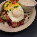Corned beef hash over biscuits with your choice of two eggs, gravy on the side