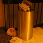 Overflowing garbage cans by the elevator.