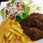 Servi en été au snack, poulet en panure épicé avec frites fraîche salade de carpaccio de cèpe.