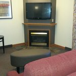 big screen TV, fireplace, couch and chair