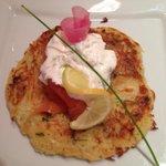 Salmon with dill yogurt on top of a potato pancake.