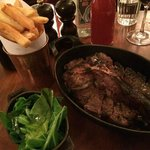 Porterhouse steak with greens and chips