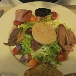 duck confit, black pudding, guissards and foie gras with salad and melon, starter.