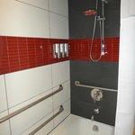 Banheiro com dispenser de sabonete, shampoo e condicionador.