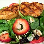 Baby Spinach Salad with Maytag bleu cheese and sliced strawberries, topped with grilled salmon