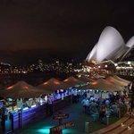 Foto serale con l'Opera House sullo sfondo e l'Opera Bar in primo piano.
