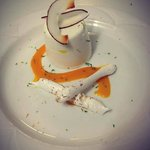 Coconut Panna cotta with mango sauce and meringue sticks.