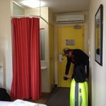 The small room behind the curtain is the shower room and the yellow door next to the entrance le