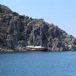 Яхта в море на фоне горы.