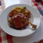 Duck Leg on a bed of Sauteed  Vegetables with Rasberry  and spiced wine sauce