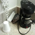 Coffee Maker with unwrapped styrofoam cups sitting directly on the vanity counter