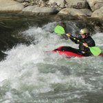 A kayaker working the rapids below a low waterfall