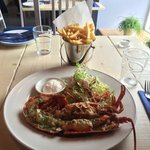 Half a Newhaven Lobster, baked, dressed and served with garlic butter,  fries and side salad.