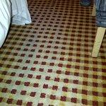 Worn carpet around the bed.