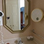 Extra vanity with hair dryer and makeup mirror outside the bathroom.