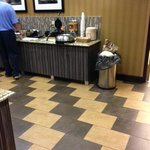 Trash bin container sitting on food counter with staff member present..
