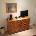 Dresser with coffee and television in the room
