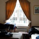 Vista de la habitación. Hay una cama que no sale. Son dos mesitas de luz pequeña. La 3er cama no