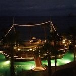 This is the pirate ship in the pool at night.